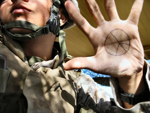 Soldier with peace symbol written on his hand